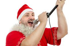 Happy guy in santa suit singing in microphone Stock Photos