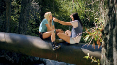 Teenage Girls Sitting, Talking On A Walk Bridge In The Forest Stock Footage