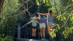 Group Of Three Teenage Girls Crossing A Forest Walk Bridge Stock Footage