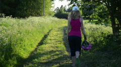Field path goes girl with white hat from sun carrying bouquet Stock Footage