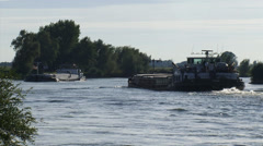 Barges passing in bend river IJssel, The Netherlands + zoom out Stock Footage