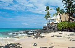 luxury hotel on untouched sandy beach with palms trees and azure ocean in bac - stock photo