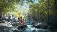 Stock Video Footage of A Group of Five Teenage Girls On Boulders Next To A Mountain Stream
