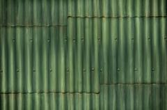 multi-tone green corrugated wall with seams and bolts add interest to the bac - stock photo