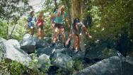 Stock Video Footage of Group of Five Teenage Girls Crossing Boulders To A Mountain Stream