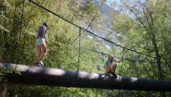 Two Teenage Girls On A Walk Bridge In A Forest Stock Footage
