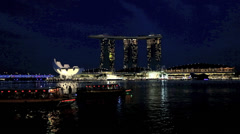 Time lapse of tourist boats at night with the Marina Bay Sands hotel in the back Stock Footage