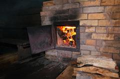 Old stove with open door and burning the wood Stock Photos