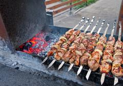 Juicy slices of meat with sauce prepare on fire (shish kebab). Stock Photos