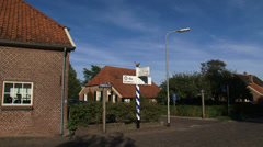 Signpost in rural village + pan street + cyclist in Dutch countryside Stock Footage