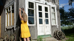 Woman in yellow dress hammering horse shoe on country house wall Stock Footage