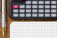 Calculator, pen and notepad on the table Stock Photos