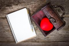 heart in the  box and notebook with a pen - stock photo