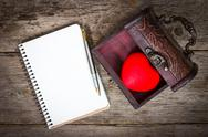 Stock Photo of heart in the  box and notebook with a pen