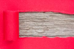 Stock Photo of red paper torn to reveal wooden panel