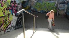 Women walk upstairs from city underground subway paint graffiti Stock Footage