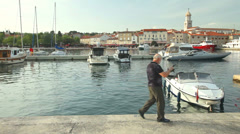 Tourist in the harbour of old town Krk in Croatia Stock Footage