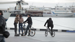 Young teens rollerblades and bicycles on the pier Stock Footage