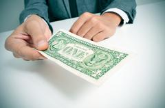 Man in suit offering a one us dollar bill Stock Photos