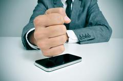businessman hitting a smartphone with his fist - stock photo