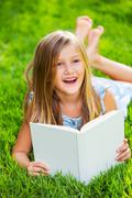 cute little girl reading book outside on grass - stock photo