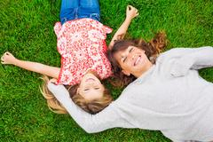 happy mother and daughter relaxing outside on green grass. spending quality t - stock photo