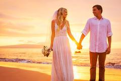 Bride and groom, enjoying amazing sunset on a beautiful tropical beach, roman Stock Photos