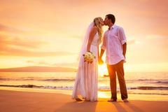 bride and groom, enjoying amazing sunset on a beautiful tropical beach, roman - stock photo