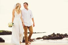 Bride and groom, romantic newly married couple holding hands walking on the b Stock Photos