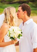 bride and groom, romantic newly married couple kissing at the beach, just mar - stock photo