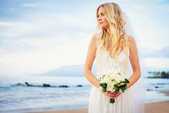 beautiful bride, gorgeous woman on tropical beach at sunset with flower bouqu - stock photo