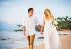 bride and groom, walking on a beautiful tropical beach at sunset, romantic ma - stock photo