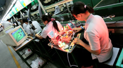 Factory worker using technology to assess product, Mainland China - stock footage