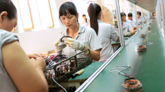 Factory assembly worker checking  product for reliability, China - stock footage