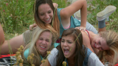 Group Of Four Teenage Girls Playing In A Pile In A Natural Setting Stock Footage
