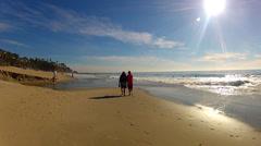 Couple Walk On Aliso Beach Next To Lapping Waves- Laguna Beach CA Stock Footage