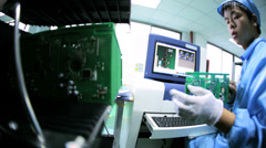 Quality control checks by Chinese worker on PCBs, China - stock footage