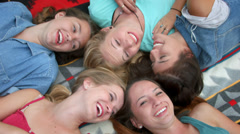 Group Of Five Animated Teenage Girls Lying On Their Backs, Giggling - stock footage