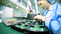 Skilled female Chinese worker manufacturing PCBs, China - stock footage