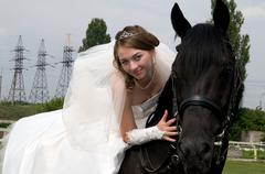 Fiancee in a wedding dress astride on a horse Stock Photos