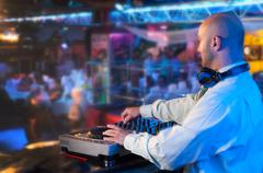 dj behind the control panel - stock photo