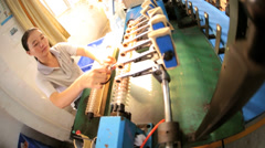 Female Chinese factory  worker operating industrial machine, China Stock Footage