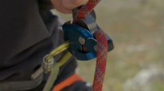 rock climbing rope passes through belay device HD - stock footage