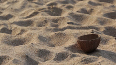 Closeup of coconut shell on sandy beach panning unpwards to out-of-focus waves - stock footage
