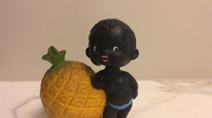 Toy Figurine Leaning On A Pineapple Nodding His Head Stock Footage