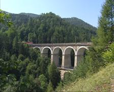 Passenger train crossing Kalte Rinne viaduct + pan excavated rocks and debris Stock Footage