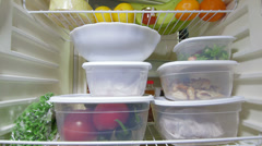 Man takes out stack of food plastic containers from fridge Stock Footage