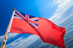Uk ensign british maritime flag of yacht sailboat blue sky sea. sailing. Stock Photos