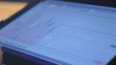Business person analyzing financial statistics on tablet screen - stock footage