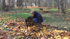 Gardener girl put autumn rake leaves in big fabric sack in yard Stock Footage